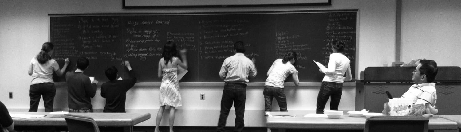 students-working-at-chalkboard-1500x430-BW